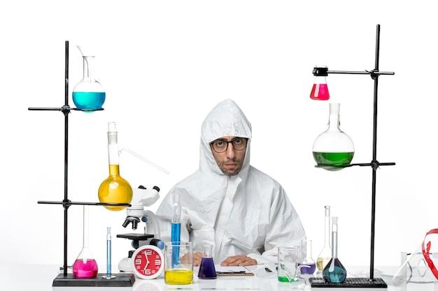 Scienziato maschio pazzo vista frontale in tuta protettiva speciale seduti attorno al tavolo con soluzioni su sfondo bianco virus della scienza di laboratorio covid malattia