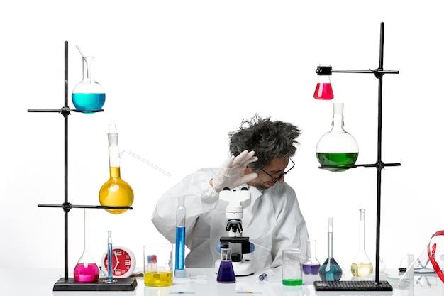 Scienziato maschio pazzo vista frontale in tuta protettiva speciale seduto intorno al tavolo con soluzioni su sfondo bianco virus scienza covid malattia di laboratorio