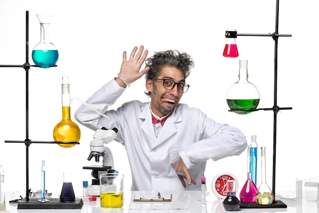 Front view crazy scientist in medical suit posing in funny manner on white background virus lab chemistry covid