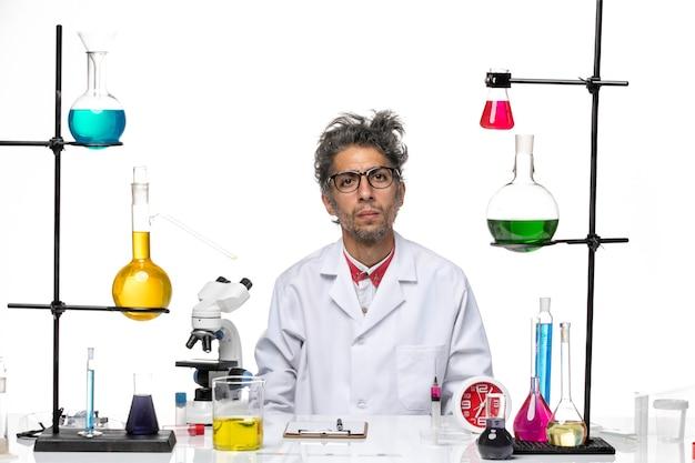 Scienziato pazzo vista frontale in tuta medica seduto con soluzioni su sfondo bianco virus laboratorio chimica covid