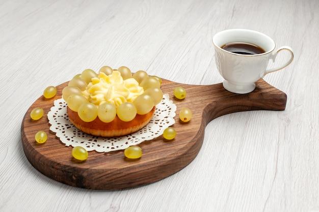 Вид спереди кремовый торт со свежим виноградом на белом фоне пирог фруктовый торт печенье печенье чай