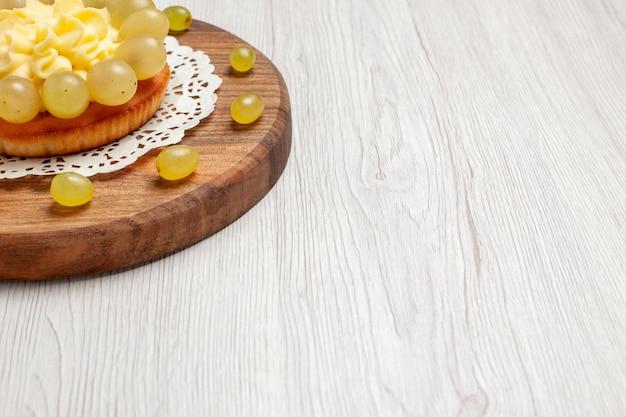 白い背景の上の新鮮なブドウと正面図のクリームケーキフルーツケーキビスケットパイクッキー