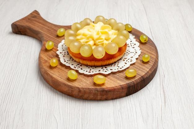 Вид спереди кремовый торт со свежим виноградом на белом фоне фруктовый торт бисквитный пирог печенье