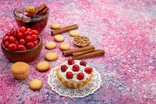 Кремовый торт, вид спереди со свежей красной клюквой, печеньем с корицей и чаем на ярком столе, сладкое печенье.