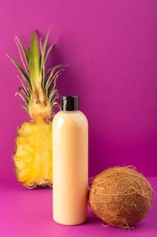 Una bottiglia di shampoo di plastica color crema vista frontale con tappo nero insieme a limoni ananas e cocco isolato su sfondo viola cosmetici bellezza frutti