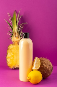 A front view cream colored bottle plastic shampoo can with black cap along with lemons pineapple and coconut isolated on the purple background cosmetics beauty fruits