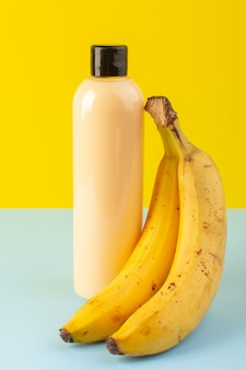 A front view cream colored bottle plastic shampoo can with black cap isolated along with bananas on the yellow-iced-blue background cosmetics beauty hair