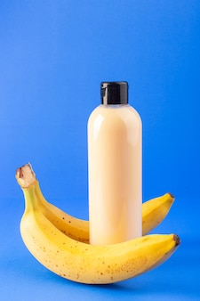 A front view cream colored bottle plastic shampoo can with black cap isolated along with coconut and bananas on the blue background cosmetics beauty hair