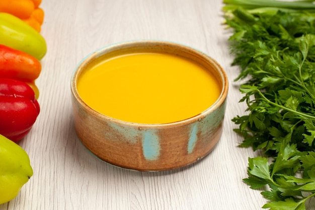 ホワイト デスク スープ ソース クリーム ディナー皿の上の緑とピーマンの正面図のクリーム スープ