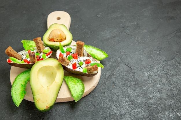 灰色の空間にパンとコショウと新鮮なアボカドを添えた正面図のクリーミーなアボカド