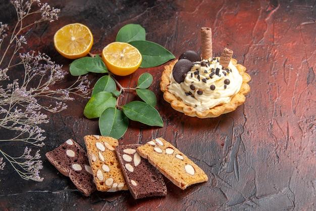 暗い背景にレモンと正面のクリーミーなケーキ
