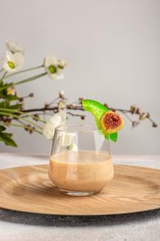 Вид спереди сливочный коктейль внутри маленького стакана на белой поверхности