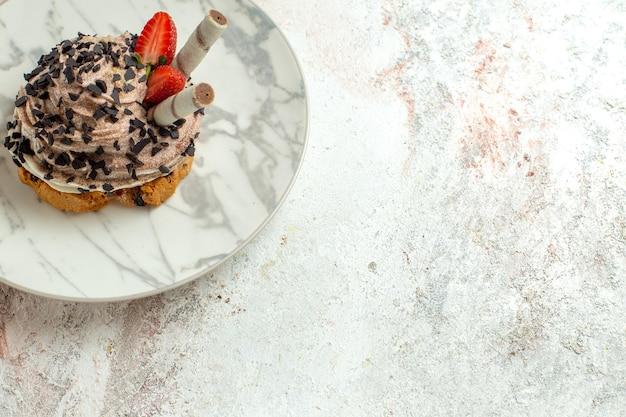 Vista frontale deliziosa torta cremosa con fragole su una superficie bianca chiara, biscotto al tè, torta di compleanno dolce
