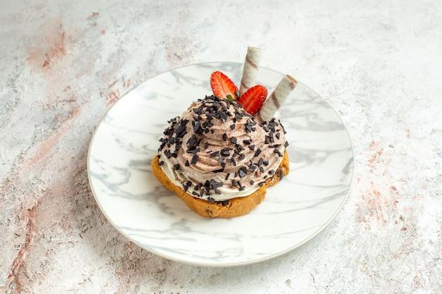 Vista frontale deliziosa torta cremosa con fragole su torta di compleanno di biscotto al tè con crema di superficie bianca dolce