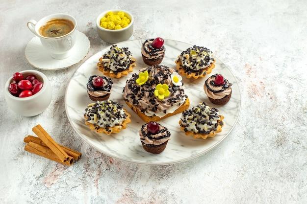 흰색 표면 차 케이크 비스킷 달콤한 생일 크림에 초콜릿 cps와 전면보기 크림 맛있는 케이크