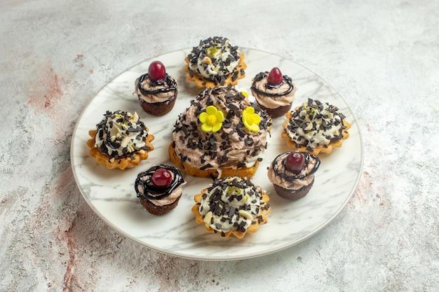 Vista frontale deliziose torte cremose con scaglie di cioccolato su superficie bianca torta biscotto biscotto tè crema dolce