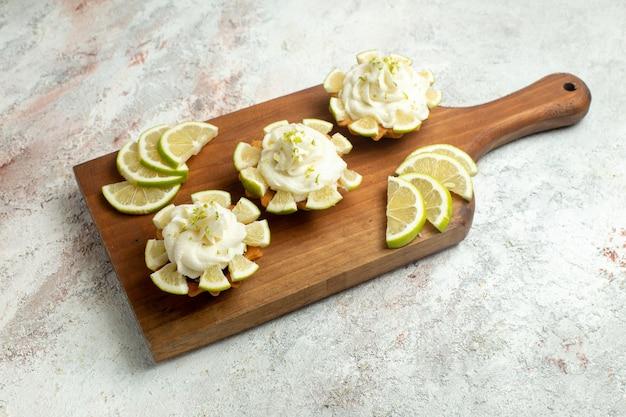 Vista frontale deliziose torte cremose con fette di limone su superficie bianca torta biscotto biscotto crema di tè dolce