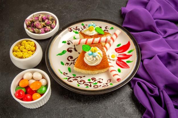 Fette di torta cremosa vista frontale con caramelle e tessuto viola su spazio grigio