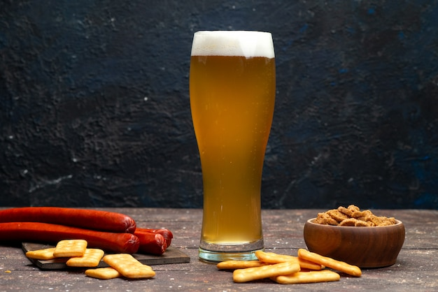 Front view of crisps and crackers along with beer on the dark surface