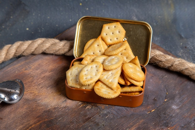 Front view of crisps and crackers on the wooden desk with ropes