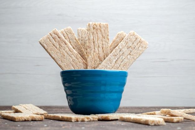 Una vista frontale patatine all'interno della ciotola sul cracker croccante sfondo bianco secco