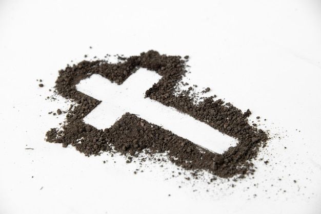 Front view of cross shape with dark soil on white surface