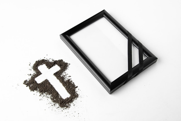 Front view of cross shape with picture frame on white surface