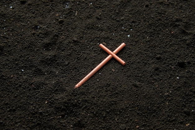 Front view of cross on soil grim reaper funeral death evil Premium Photo