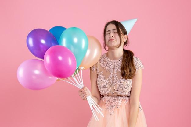 風船を保持しているパーティーキャップと正面図泣いている女の子