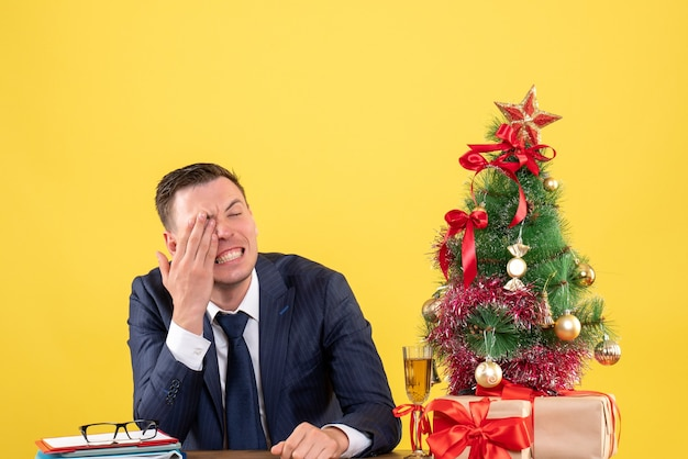 Front view of crying man covering his eye with hand sitting at the table near xmas tree and gifts on yellow