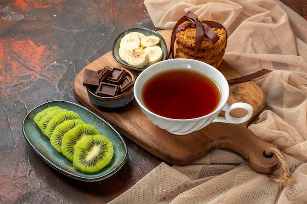 Vista frontale di una tazza di tè nero impilati biscotti frutta tritata barrette di cioccolato su tagliere di legno su colore misto
