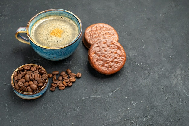 Front view a cup of coffee bowl with coffee seeds biscuits on dark isolated background free place