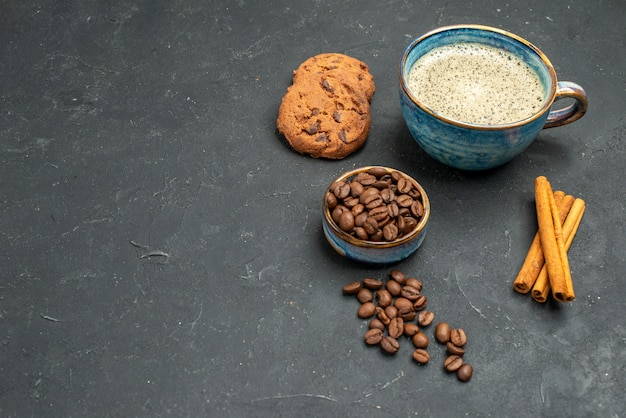 Front view a cup of coffee bowl with coffee seeds cinnamon sticks biscuits on dark isolated background free place