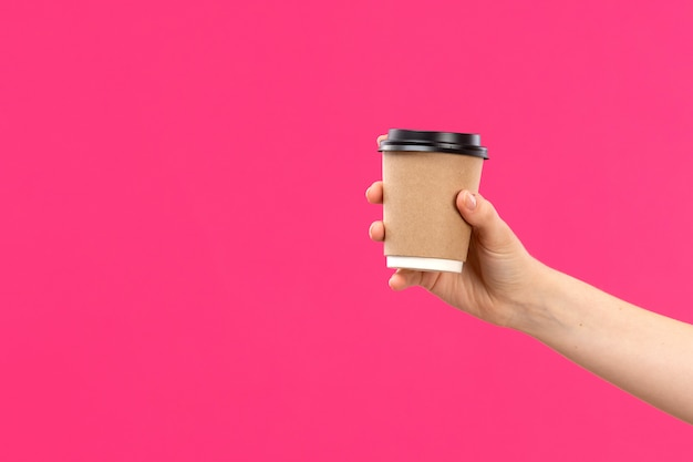 A front view cup of coffee hand holding coffee male hand pink background color drink
