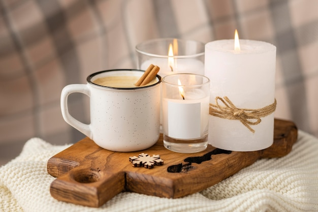 Front view of cup of coffee with cinnamon sticks and candles