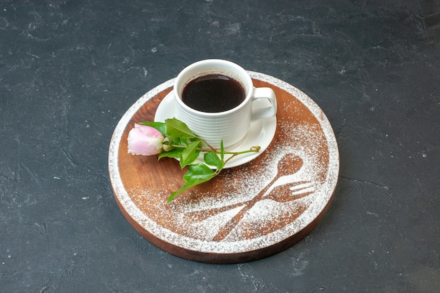Front view cup of coffee with flower and flour on a dark wall