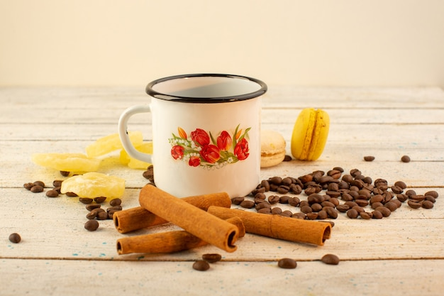 A front view cup of coffee with fresh brown coffee seeds cinnamon crackers on the light surfacedrink coffee caffeine