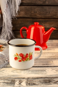 Front view of cup of coffee with red kettle on the wooden desk