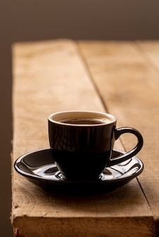 Front view cup of coffee on wooden table