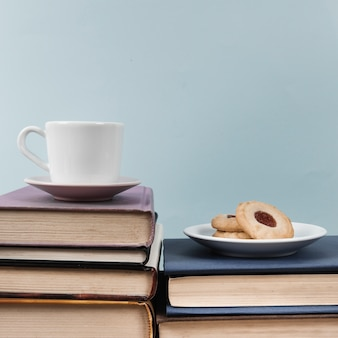 Front view of cup and cookie on books with plain background