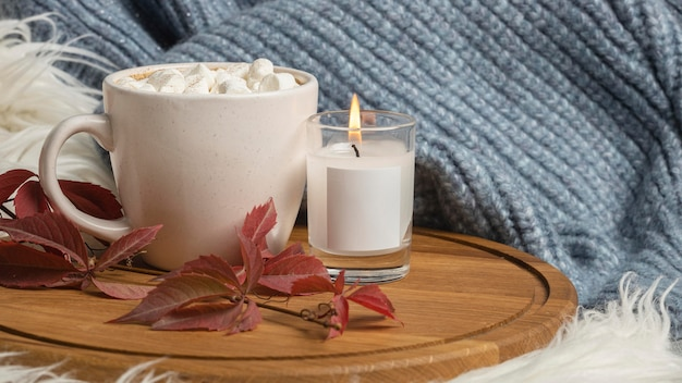 Front view of cup of hot cocoa with marshmallows and candle