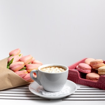 Front view of cup of marshmallows with tulips and macarons