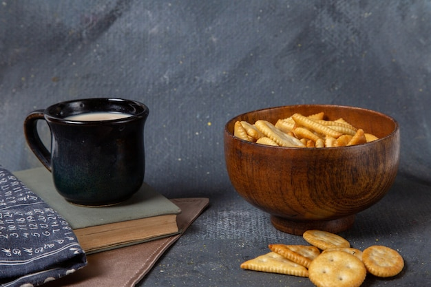 Front view of cup of milk black cup with salted crackers on the grey surface