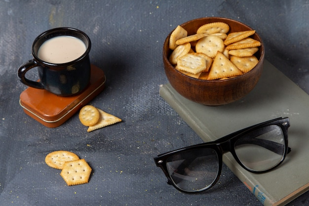 Front view of cup of milk with crackers and sunglasses on the grey surface