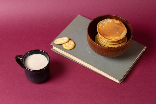 Vista frontale della tazza di latte con pancake e cracker sulla superficie rosa