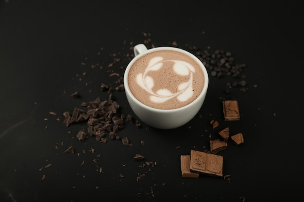Чашка капучино с шоколадом на черной поверхности вид спереди