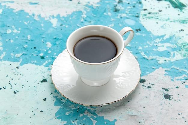 Вид спереди чашка кофе горячего и крепкого напитка на голубой поверхности пить кофе какао цветное фото