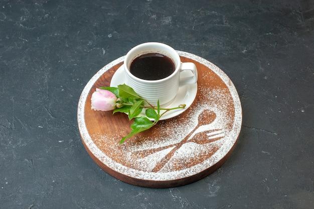 어두운 벽에 꽃과 밀가루를 넣은 커피 한 잔