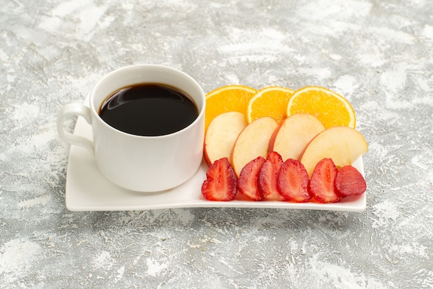 밝은 흰색 배경에 과일 잘 익은 신선한 부드러운 슬라이스 사과 오렌지와 딸기와 커피의 전면보기 컵