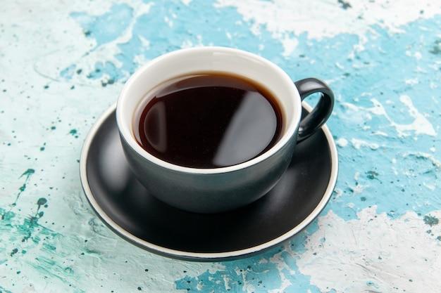 Вид спереди чашка чая с горячим напитком внутри чашки и тарелки на синей поверхности